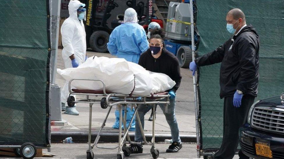 Un hombre lleva un cadáver en una camilla