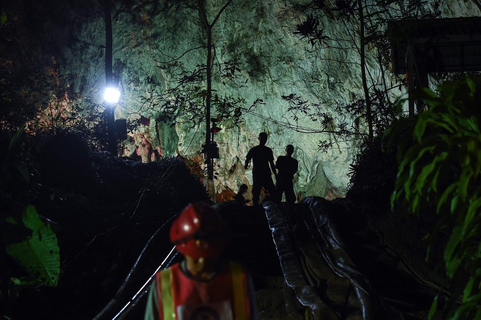 Thai soldiers stand at the mouth of Tham Luang cave