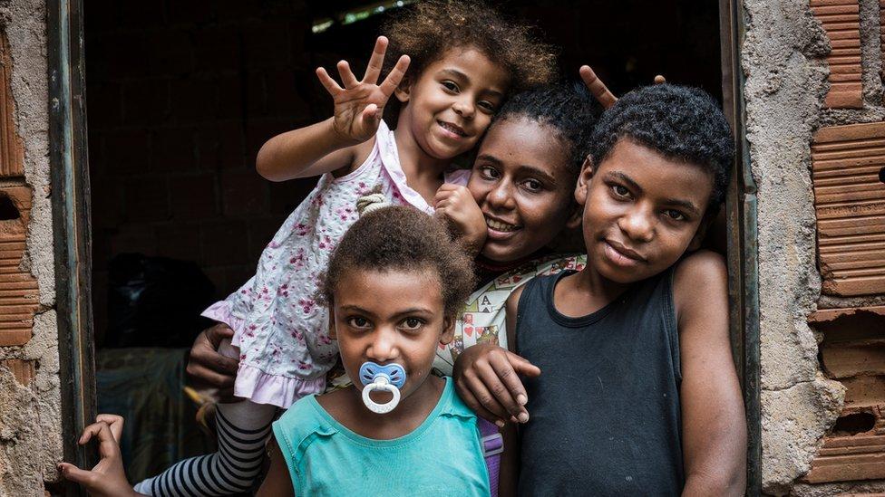 Um menino e três meninas negras no batente de uma porta em casa de tijolos sem acabamento