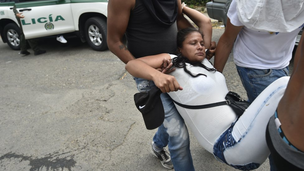 A demonstrator affected by tear gas is carried out from the Simon Bolivar international bridge, in Cucuta, Colombia,