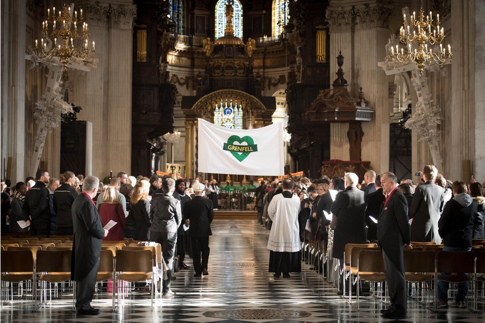 A Grenfell banner being carried into the cathedral