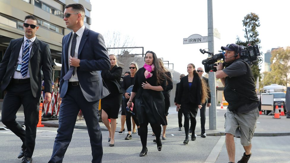 Prosecutors and detectives cross a road in front of a Perth courthouse for the Claremont murder trial in September
