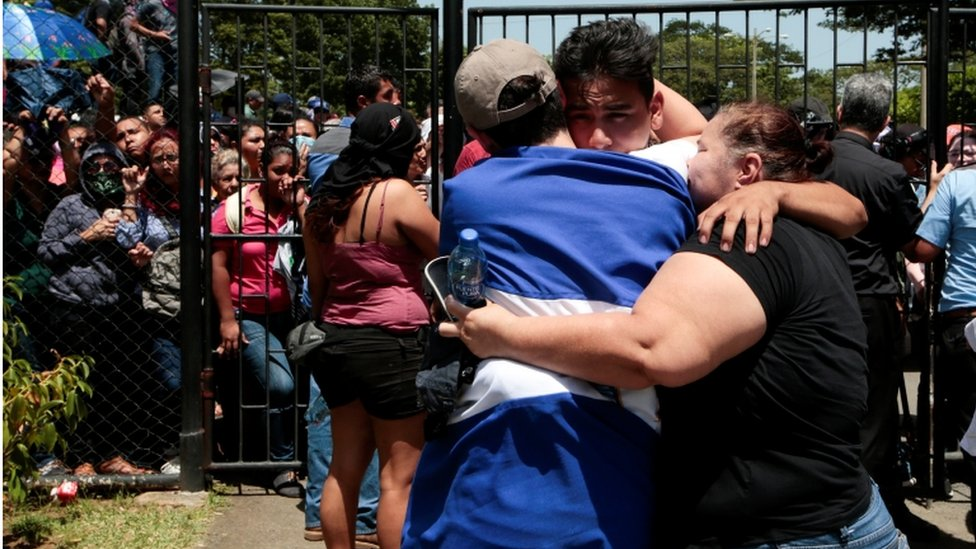 Una mujer se abraza con dos hombres frente a una multitud detras de las rejas en Managua.
