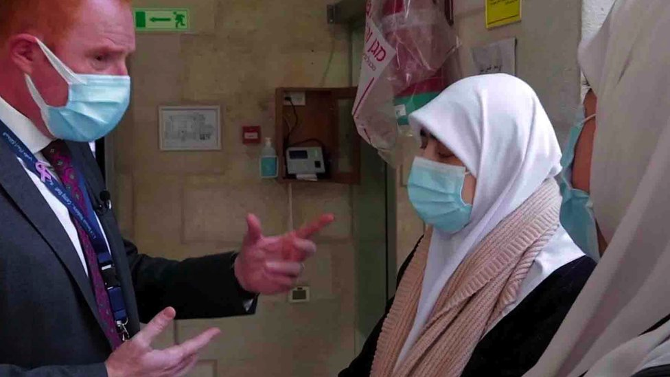Dr Fadi speaks to two patients wearing masks