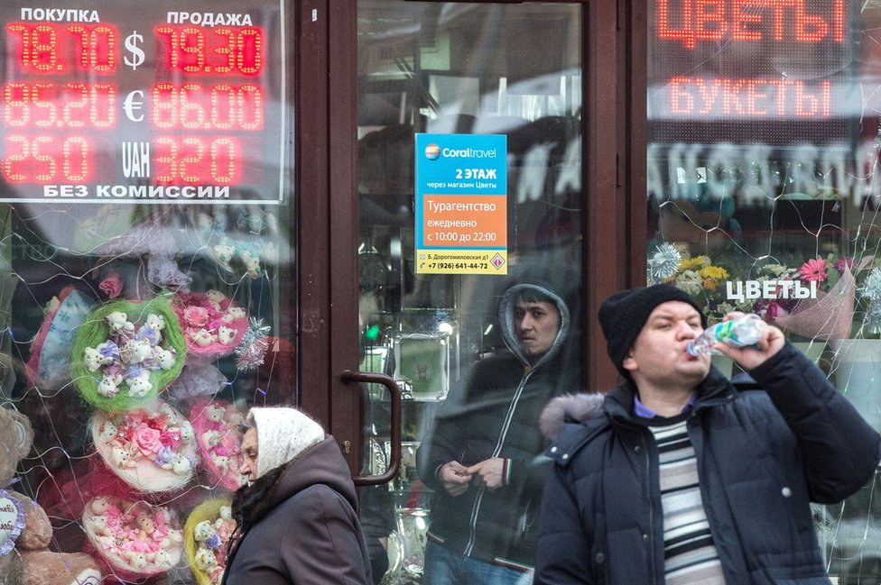 Pedestrians walk past boards listing foreign currency rates against the Russian rouble outside an exchange office in Moscow on 18 January 2016.