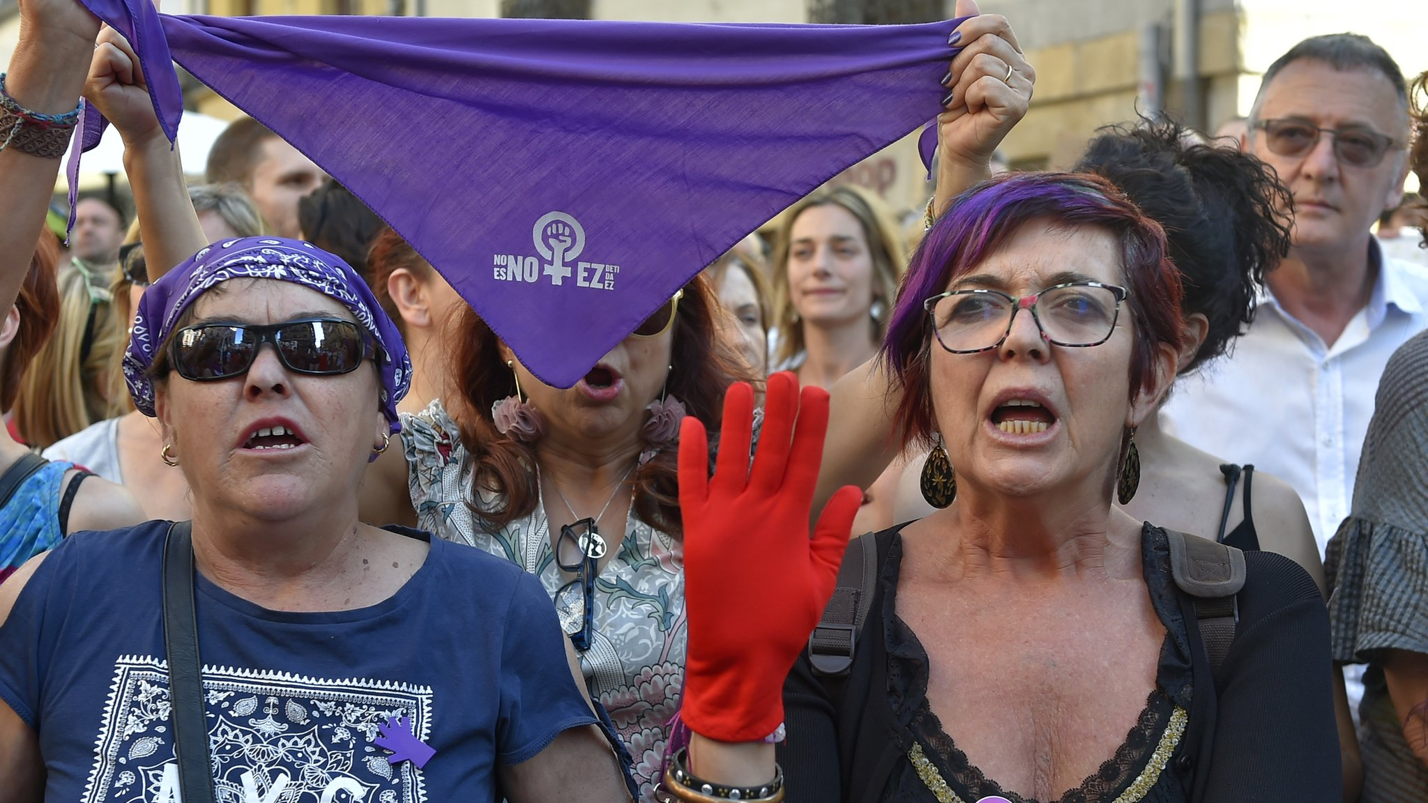 Demonstrators (mostly women) protest, one of them wearing a red glove in Pamplona (June 21, 2018)