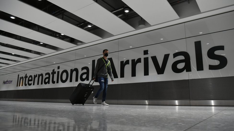 Un hombre con mascarilla llegando a Heathrow.
