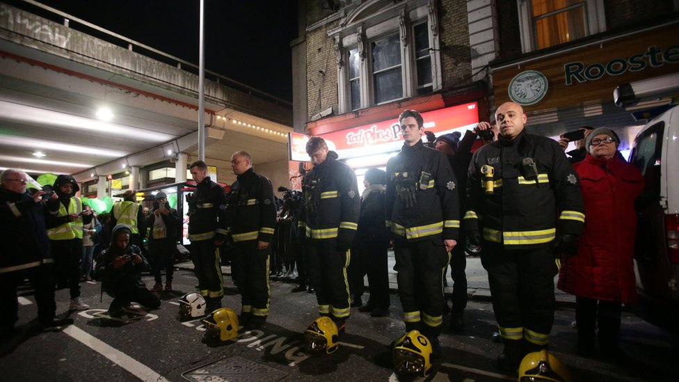 Firefighters stand to attention