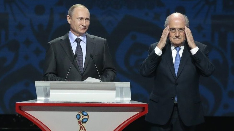Sepp Blatter (right) adjusts his glasses during a speech by Russian President Vladimir Putin during the preliminary draw for the 2018 soccer World Cup in St Petersburg (25 July 2015)