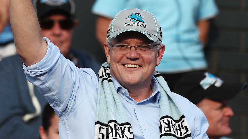 Scott Morrison wearing a baseball cap and rugby scarf waves to the crowd while celebrating his victory at a rugby league match in Sydney on Sunday