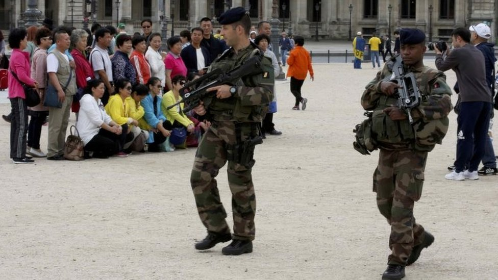 Chinese tourists take group pictures as French army soldiers patrol near the Louvre Museum Pyramid's main entrance in Paris (19 August 2016)