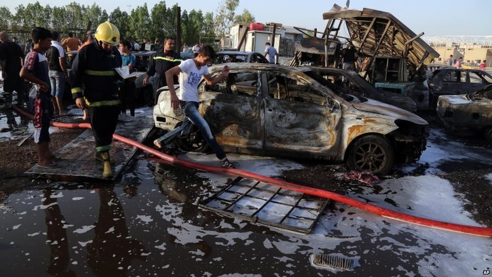 Civilians and security forces gather at the scene of a deadly car bomb in the Habibiya area of Sadr City, Baghdad 15/08/2015