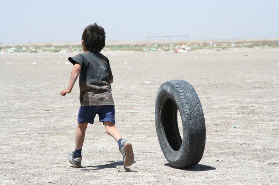 Niño jugando con un neumático.