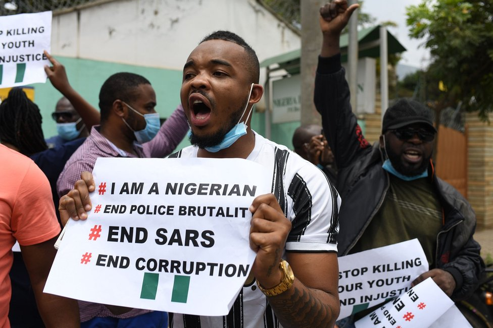 A man holds up a sign as people gather to protest outside the Nigerian embassy in Nairobi