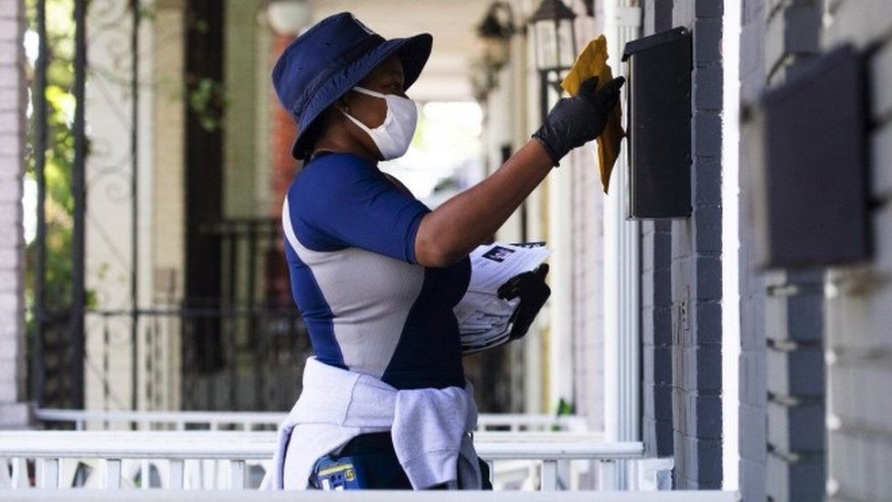 A US Postal Service worker puts mail in a letter box