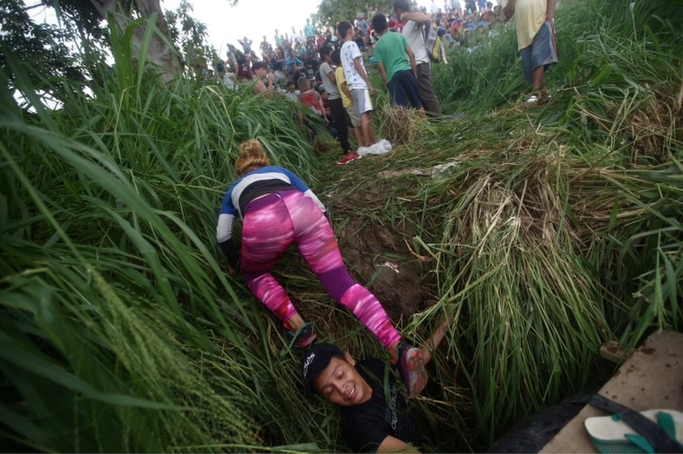 A woman crawls onto the riverbank after crossing the Suchiate River with the help of fellow migrants