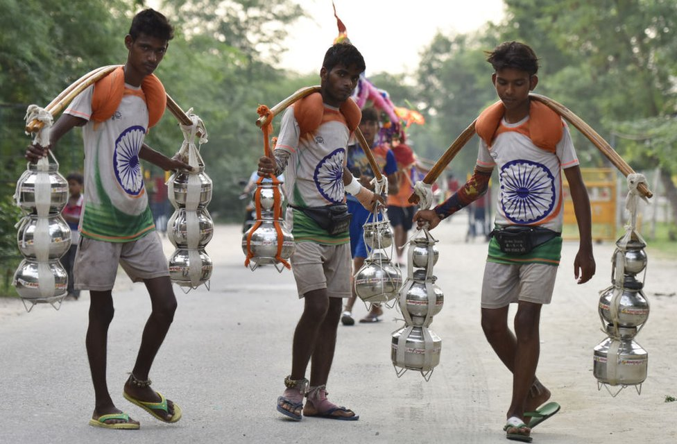 Kanwariyas wearing t-shirts with the Indian national flag printed on them carry holy water in pots on 19 July 2017.