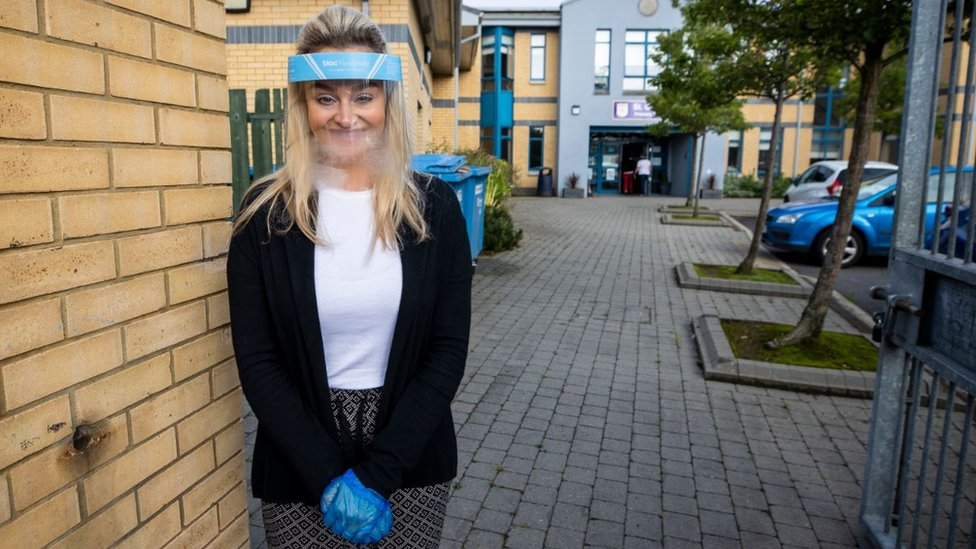 Ashleigh Clarke, teacher at St Clare's Primary School in Belfast, wearing a protective visor and gloves on Monday 24 August, as P7 pupils are allowed to return to school in Northern Ireland