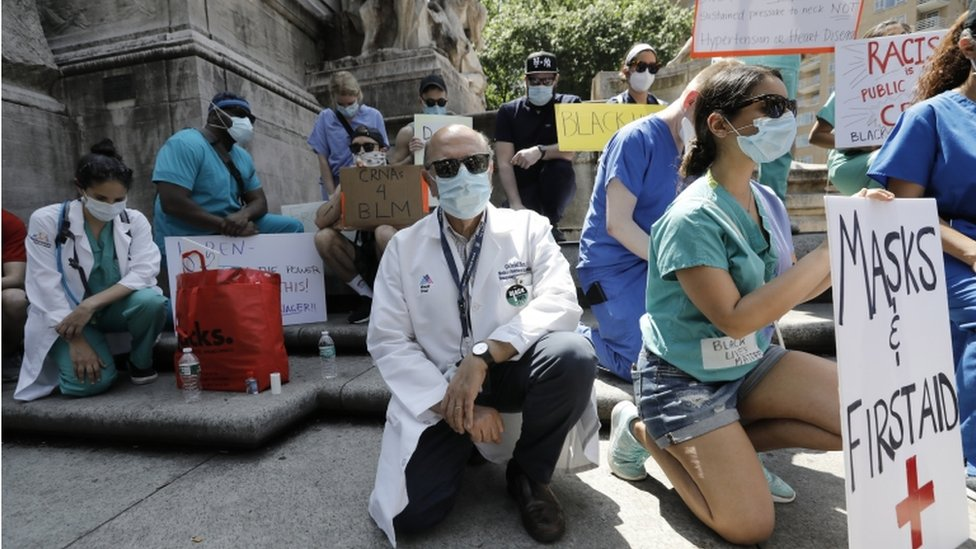 Healthcare workers kneel in silence during a protest at Columbus Circle, 12 days on after George Floyd