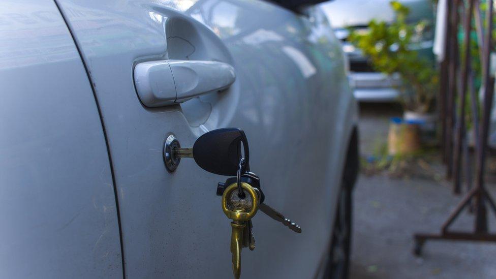 Una puerta de un auto con las llaves puestas.