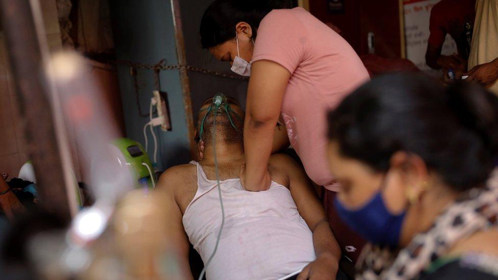 امرأة هندية تضغط على صدر والدها الذي يعاني صعوبة في التنفس
