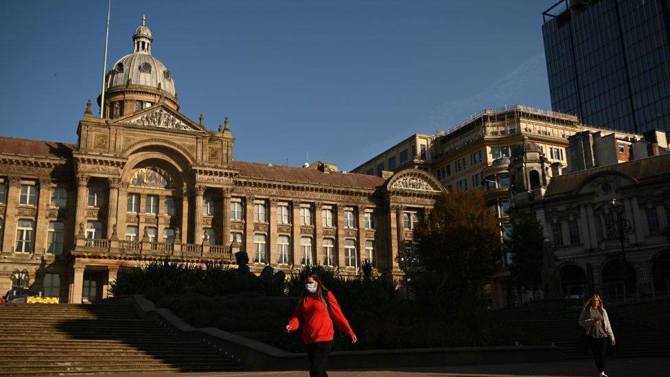 A woman walks past Birmingham's town hall