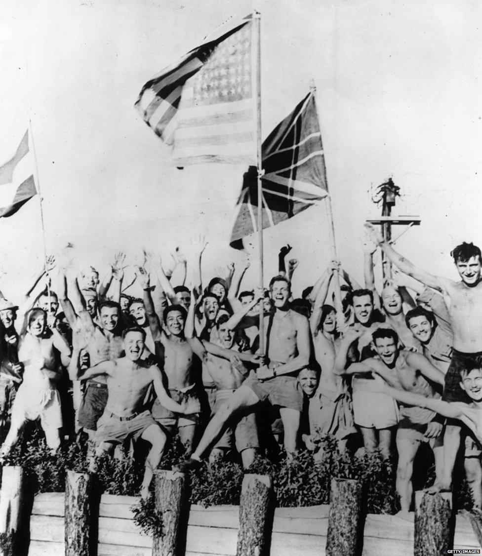 1945年8月29日,在日本青森戰俘營中的盟軍士兵揮舞美國、英國和荷蘭國旗歡呼迎接美國海軍運載糧食、衣服和藥品的救援部隊。