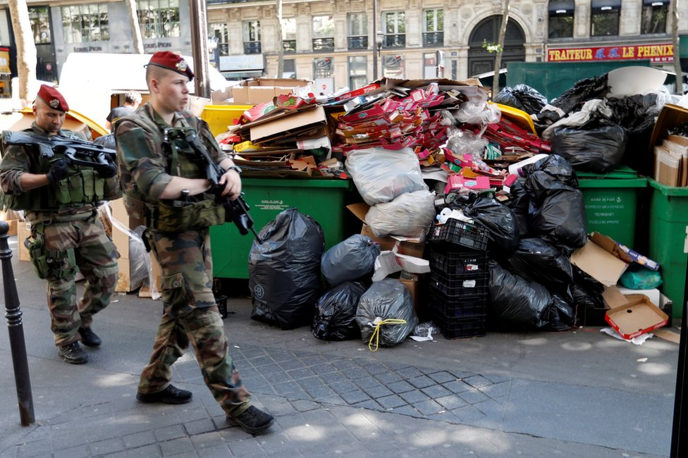 French soldiers pass uncollected rubbish in Paris, 9 June