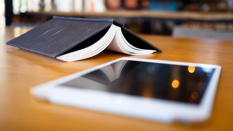 Un libro abierto y una tablet