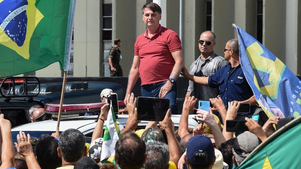 O presidente Jair Bolsonaro se prepara para falar depois de se juntar a seus apoiadores que participavam de uma carreata em protesto contra medidas de quarentena e distanciamento social para combater o novo surto de coronavírus em Brasília em 19 de abril de 2020. (Foto EVARISTO SA / AFP)