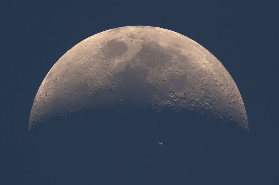 The International Space Station (ISS) whizzes across the dusky face of the moon