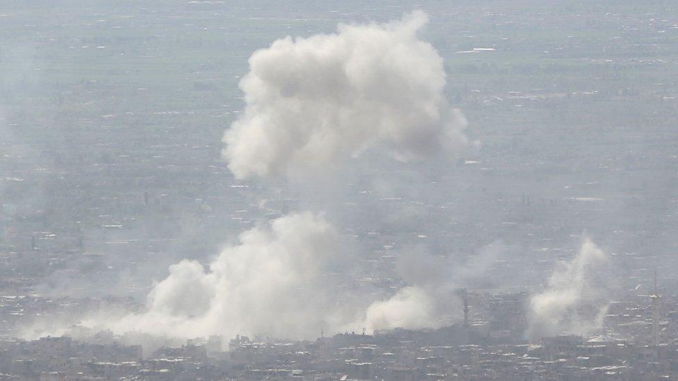 Una columna de humo se alza sobre Douma tras los bombardeos del gobierno ocurridos el 7 de abril.