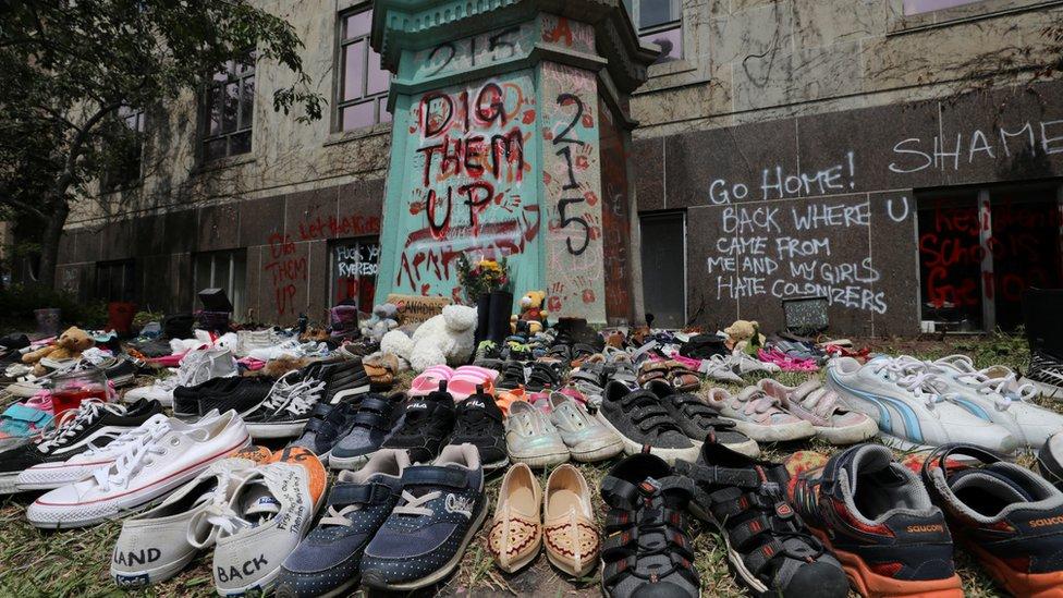 أحذية أطفال تُركت في تأبين للأطفال الذين عُثر على رفاتهم