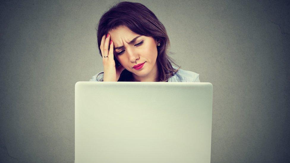Mujer mirando computadora con cara de preocupada.