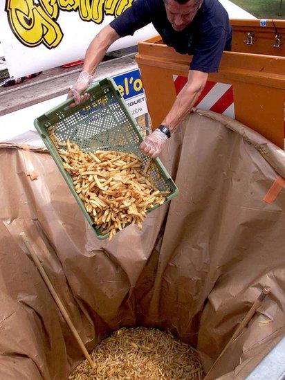 Hombre echando papas fritas a un contenedor gigante