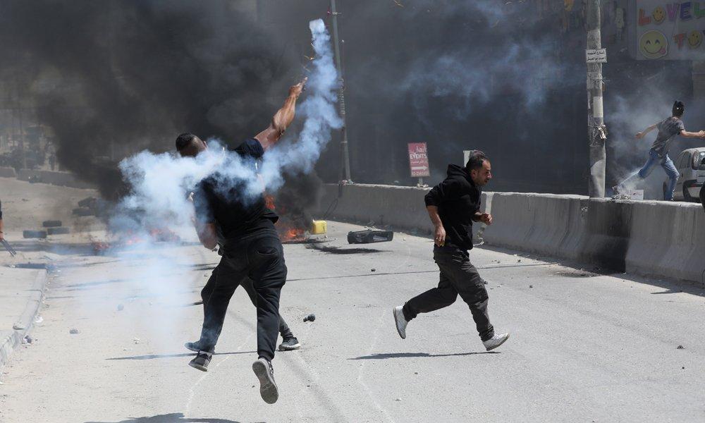 Un manifestante palestino devuelve una granada de humo que ha sido lanzada por las tropas israelíes