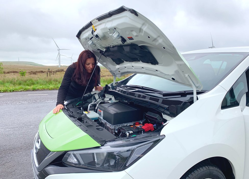 Angie Brown looking at the battery in an electric car