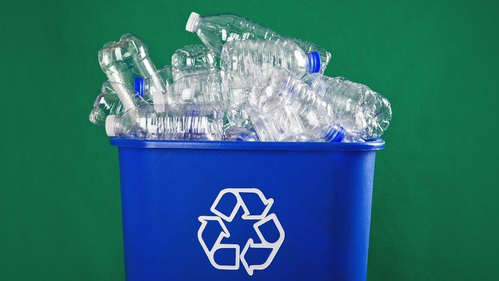 Basurero lleno de botellas de plástico