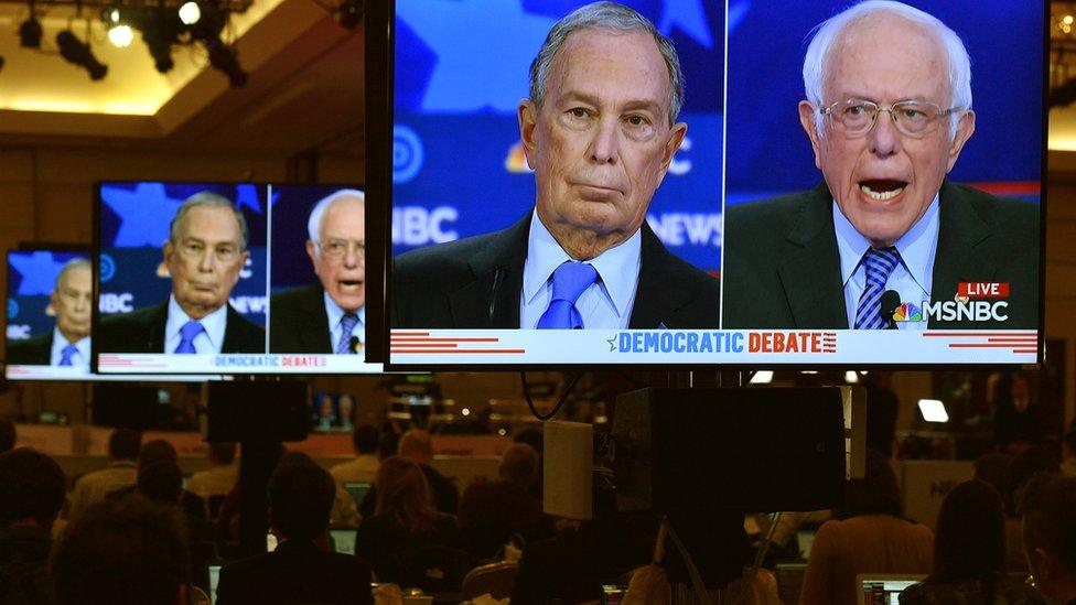 Pantalla mostrando a Bloomberg y Sanders