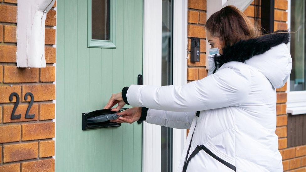 A voluntária Hanna Taylor entrega kits de teste de coronavírus de porta em porta em Woking, Surrey