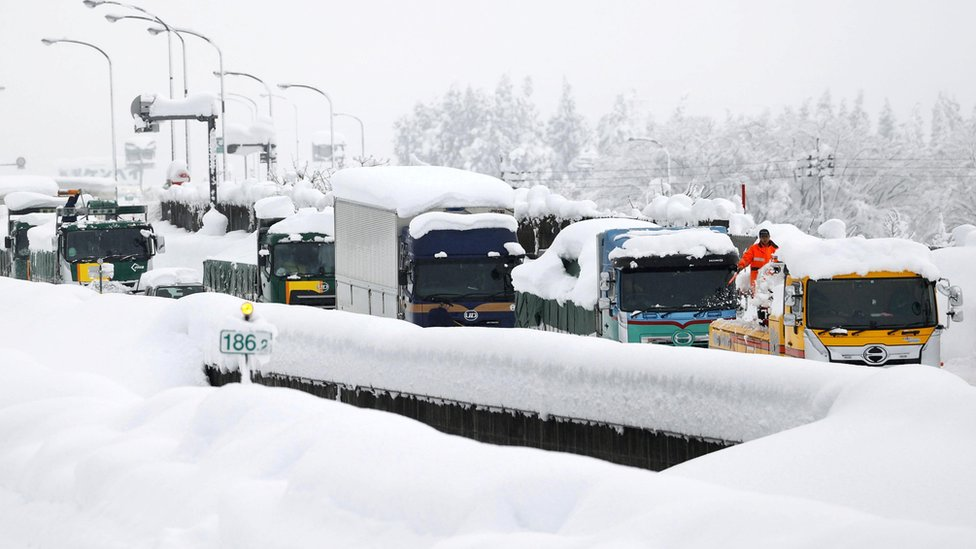 Vehicles are stranded on the snow-covered Kanetsu expressway in Minamiuonuma in Niigata Prefecture,