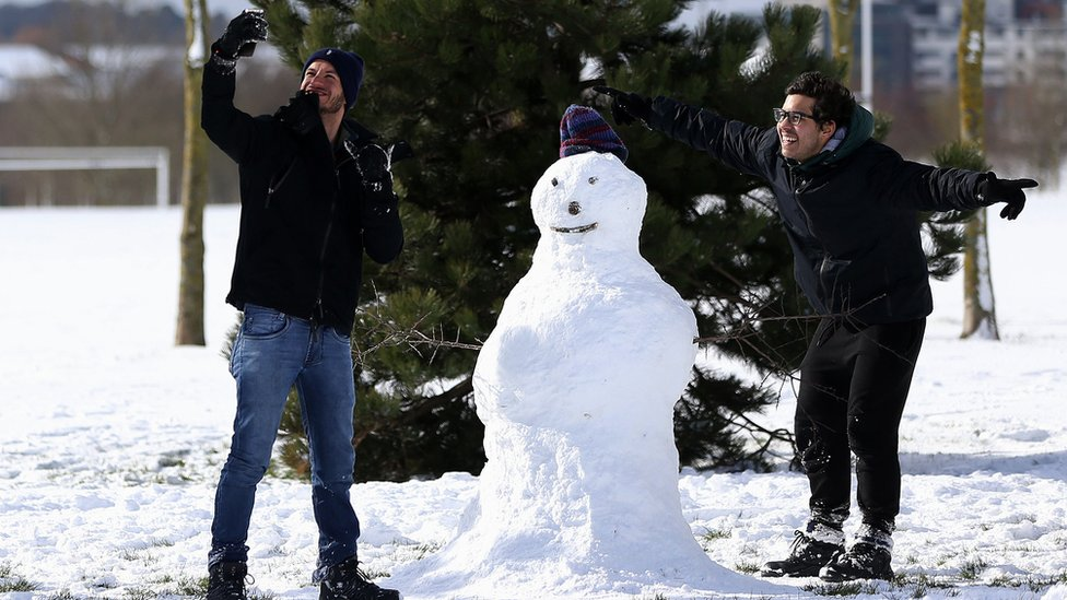 Weriskles Inacio (left) and Matheus Pires, from Sao Paulo, Brazil, take a selfie with their snowman