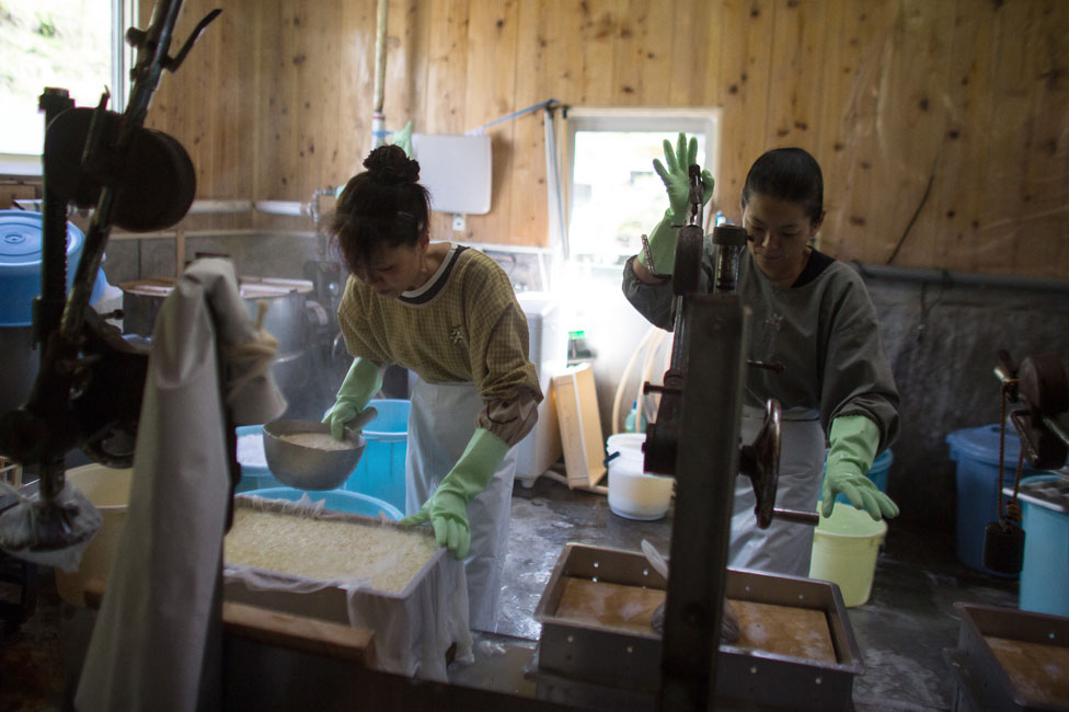 Women work in a small tofu factory, one of the few remaining businesses in her village, on April 22, 2016 in Ochiai, Miyoshi, Japan