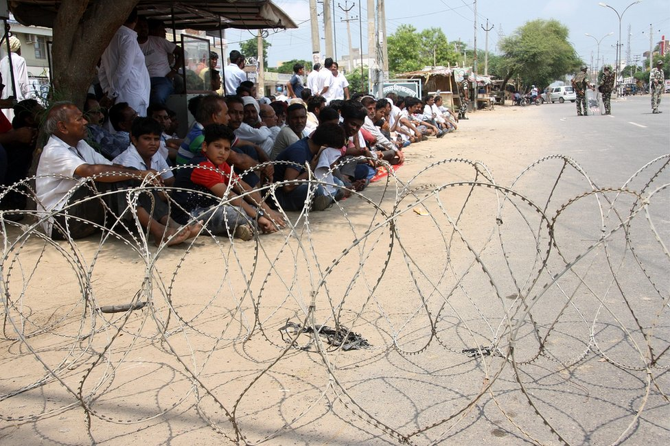 Mr Singh's supporters sit beyond barbed wire