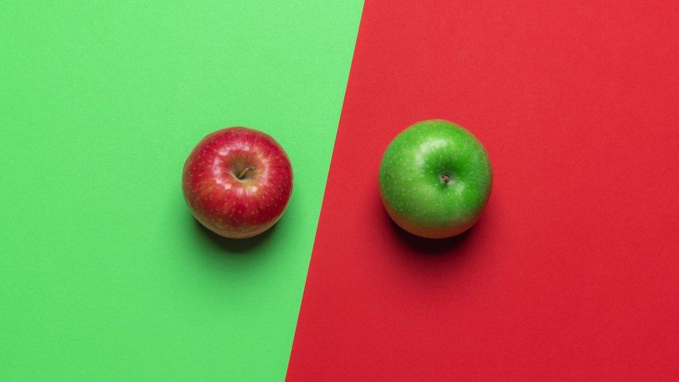 Imagen de una manzana roja sobre un fondo verde y de una manzana verde sobre un fondo rojo.