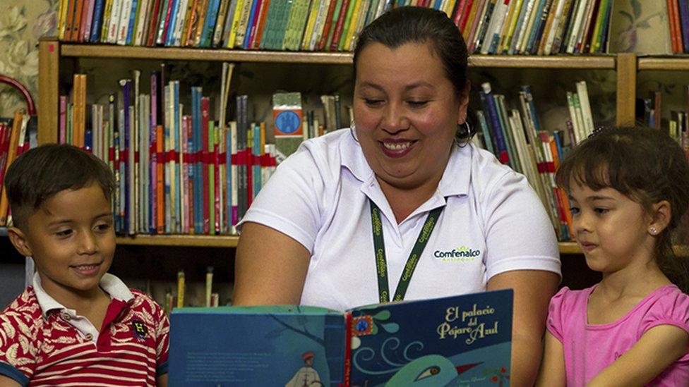 Una mujer lee un libro a unos niños en Medellín