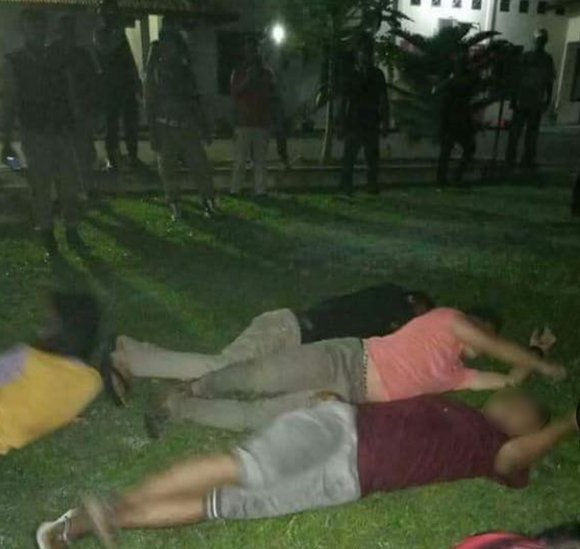The transgender women lying on the floor, surrounded by police officers, after being arrested