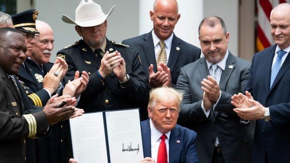 Donald Trump mostrando su orden ejecutiva firmada