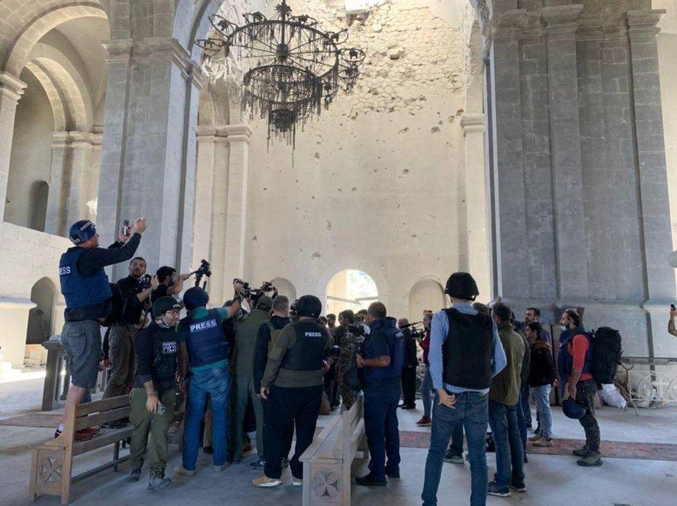 納戈爾諾—卡拉巴赫地區舒沙市記者爭相拍攝一對新人在滿布彈痕的教堂廢墟內行禮結婚(26/10/2020)