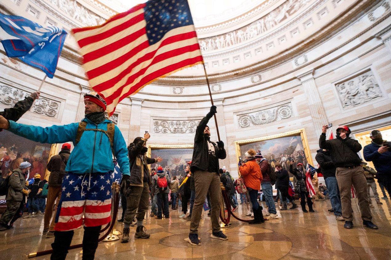 Los manifestantes llenan la rotonda del edificio del Capitolio de EE. UU. Con una bandera de EE. UU.